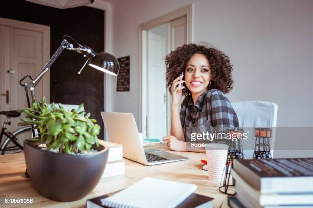 young businesswoman at home office talking on cell phone - izusek stock pictures, royalty-free photos & images