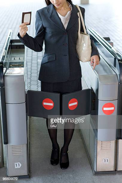 Young businesswoman blocked by turnstile at station