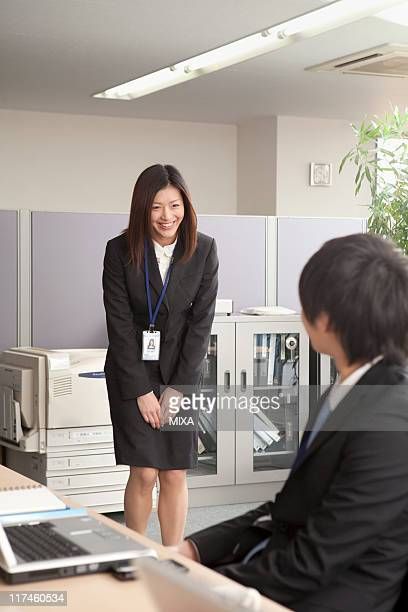 Young businesswoman bowing to young businessman