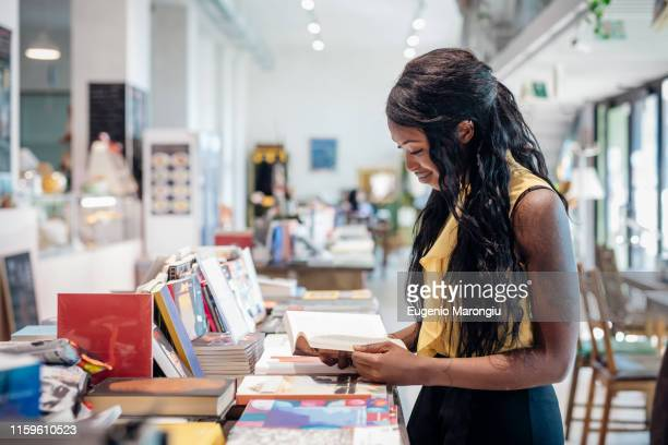 young businesswoman browsing book in bookshop - book shop stock pictures, royalty-free photos & images