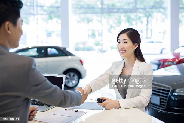 Young businesswoman buying car in showroom