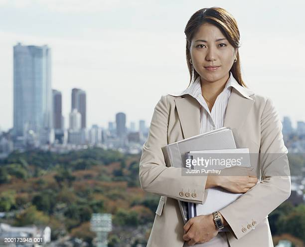 Young businesswoman by window overlooking cityscape, portrait