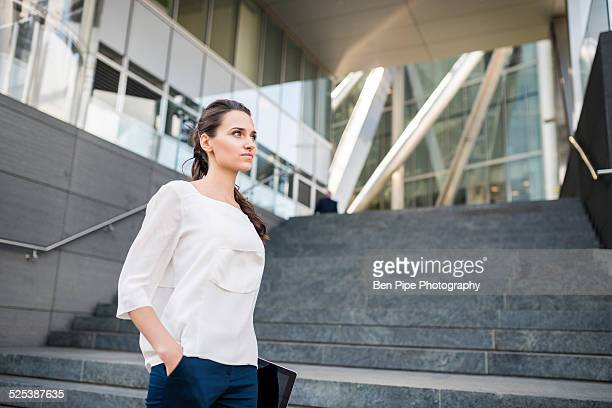 Young businesswoman carrying digital tablet, London, UK