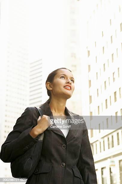 young businesswoman carrying purse, looking up - schiff stock photos and pictures