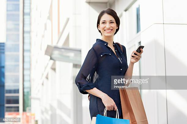 Young businesswoman carrying smartphone and shopping bags