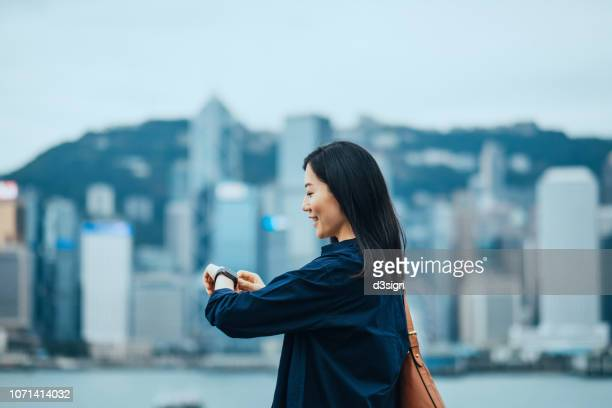 Young businesswoman checking her schedule on smartwatch by the harbour against city scene