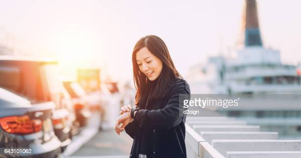 Young businesswoman checking her smart watch in city by the cruise terminal