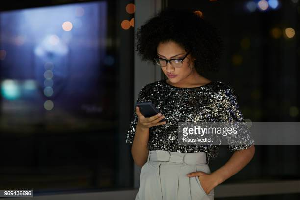 Young businesswoman checking smartphone in the office at night