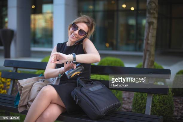 Young businesswoman checking the time on her wristwatch