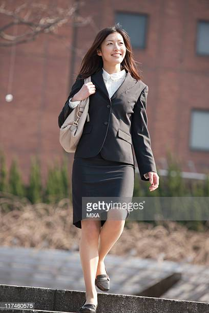 Young businesswoman climbing down stairs