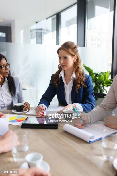Young businesswoman conducting business meeting in board room.