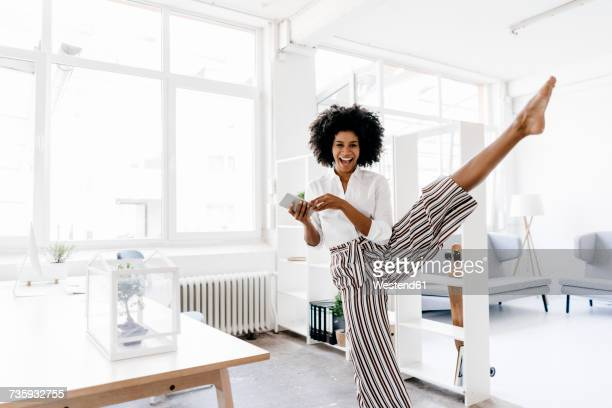 Young businesswoman dancing in her office