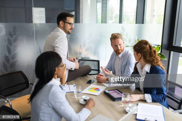 Young businesswoman discussing sale analysis with colleagues