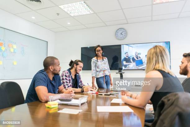 Young businesswoman discussing with colleagues in board room at creative office