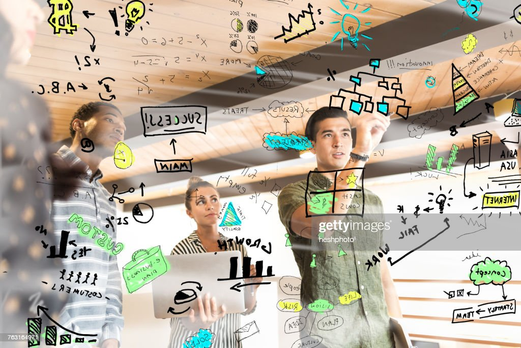 Young businesswoman drawing diagrams on glass wall in creative office : Stock Photo