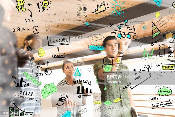 Young businesswoman drawing diagrams on glass wall in creative office