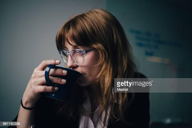 young businesswoman drinking coffee at creative office - werkneemster stockfoto's en -beelden