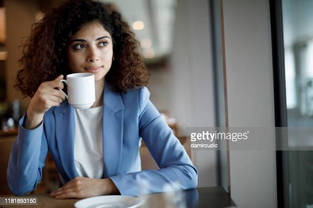 young businesswoman drinking coffee at the cafe - damircudic stock photos and pictures