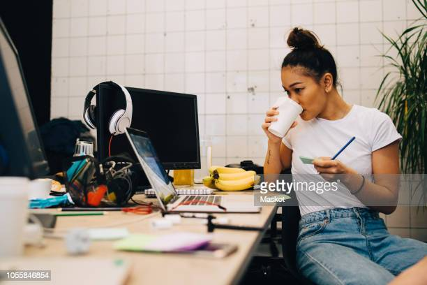 young businesswoman drinking coffee while sitting at desk in small creative office - デザイナー ストックフォトと画像