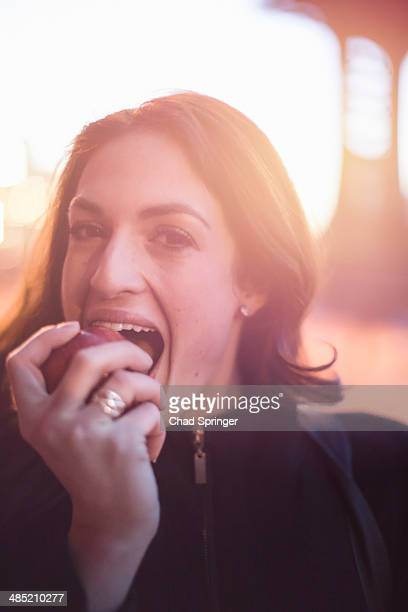 Young businesswoman eating an apple on the street