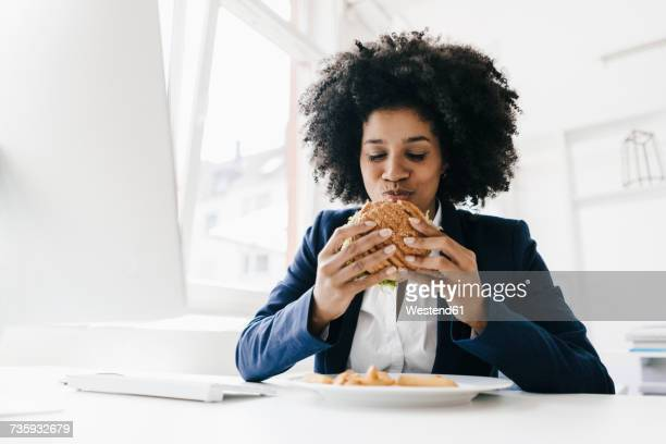 young businesswoman eating hamburger at her desk - indulgence stock pictures, royalty-free photos & images
