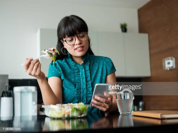 young businesswoman eating salad in lunch room and using phone - almoço imagens e fotografias de stock