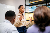 Young businesswoman explaining and gesturing in meeting
