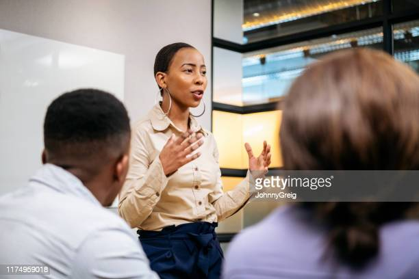 young businesswoman explaining and gesturing in meeting - leading stock pictures, royalty-free photos & images