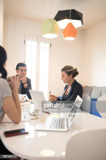 young businesswoman explaining at team meeting - heshphoto stock pictures, royalty-free photos & images