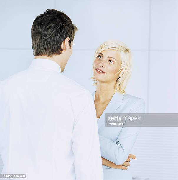 Young businesswoman facing businessman, smiling (focus on woman)