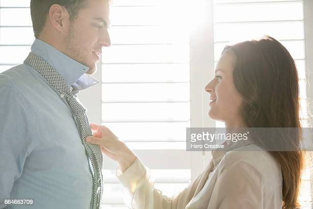 Young businesswoman fastening business boyfriends tie