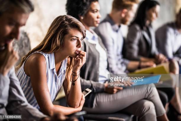 joven empresaria sintiéndose preocupada mientras espera la entrevista de trabajo. - impaciente fotografías e imágenes de stock