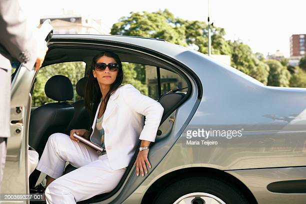 Young businesswoman getting out of back seat of car