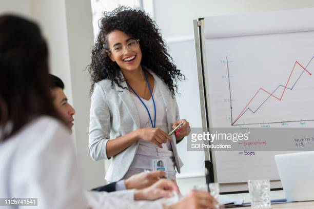 young businesswoman gives presentation to colleagues - awards ceremony stock pictures, royalty-free photos & images