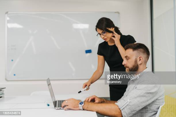 young businesswoman giving explanations to her coworker in modern office - economist stock pictures, royalty-free photos & images