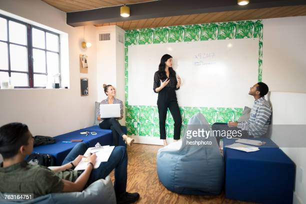 young businesswoman giving whiteboard presentation in creative meeting room - heshphoto stock pictures, royalty-free photos & images