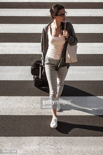 young businesswoman goes through the zebra crossing and pulls a small suitcase with a laptop bag on it - strisce pedonali foto e immagini stock