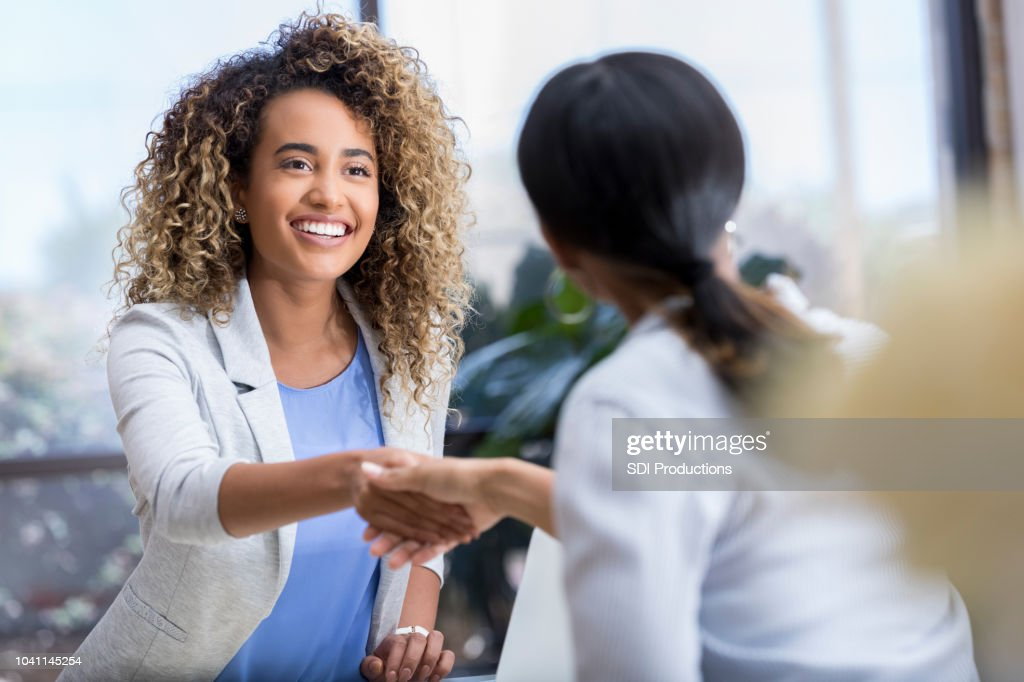 Young businesswoman greets colleague : Stock Photo