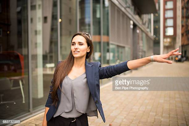 Young businesswoman hailing a cab outside office, London, UK