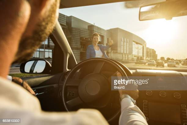 Young businesswoman hitchhiking for a ride.