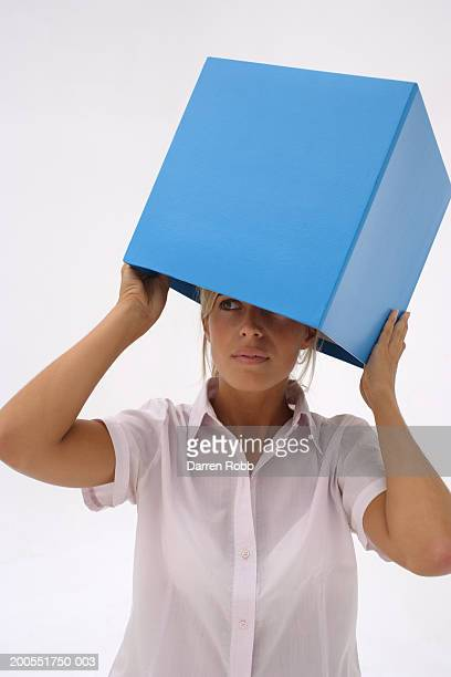 Young businesswoman holding blue box on head