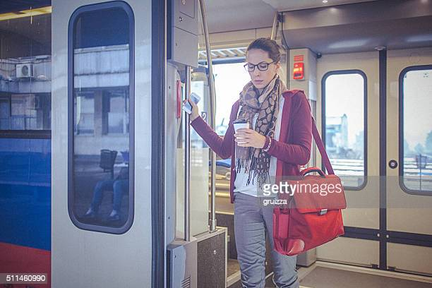 Young businesswoman holding coffee, leaving the train