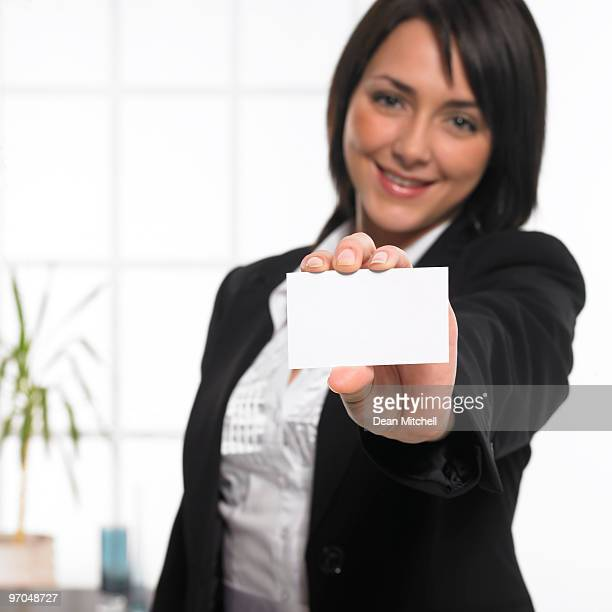 young businesswoman holding empty business card in modern office