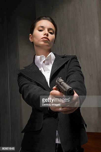 Young businesswoman holding gun