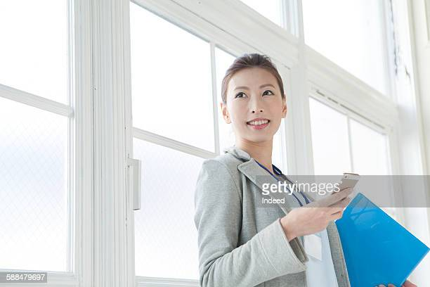 Young businesswoman holding mobile phone