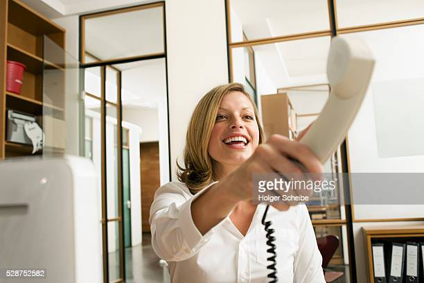Young businesswoman holding out a telephone receiver