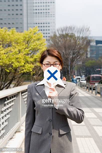 Young businesswoman holding paddle with cross over face, portrait