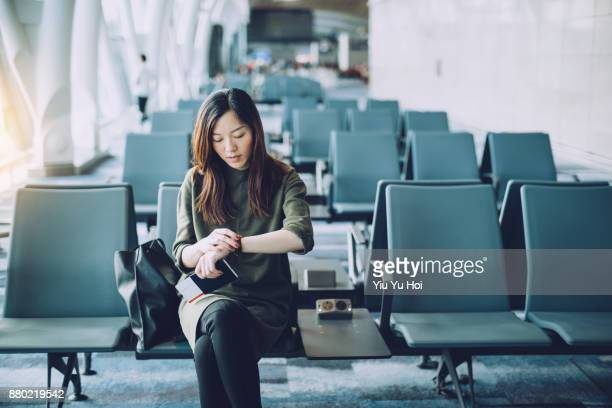 young businesswoman holding passport and boarding pass on hand, checking wristwatch in airport - wachten stockfoto's en -beelden