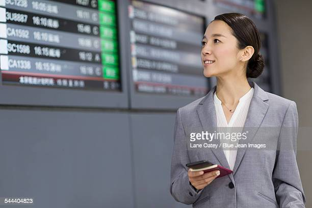 Young businesswoman holding passport and smart phone in airport