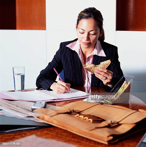 Young businesswoman holding sandwich whilst working at desk